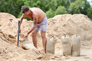 Barry Simmonds fills up sandbags in preparation for Cyclone Debbie in Townsville. Photo / AAP
