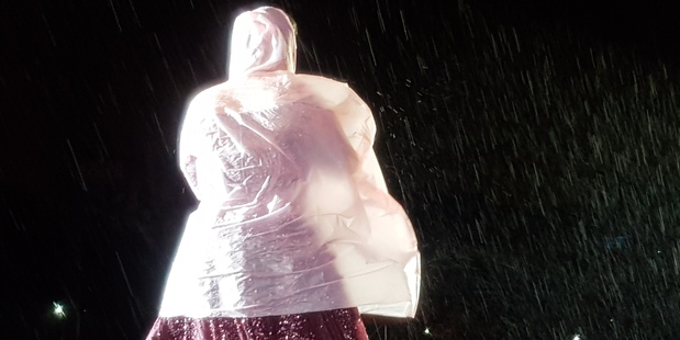 Adele dons a poncho to perform in the rain at Mt Smart Stadium in Auckland.