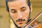 Ameen Mokdad played his violin in the innermost room of his home in Mosul with blankets on the windows to muffle the sound.