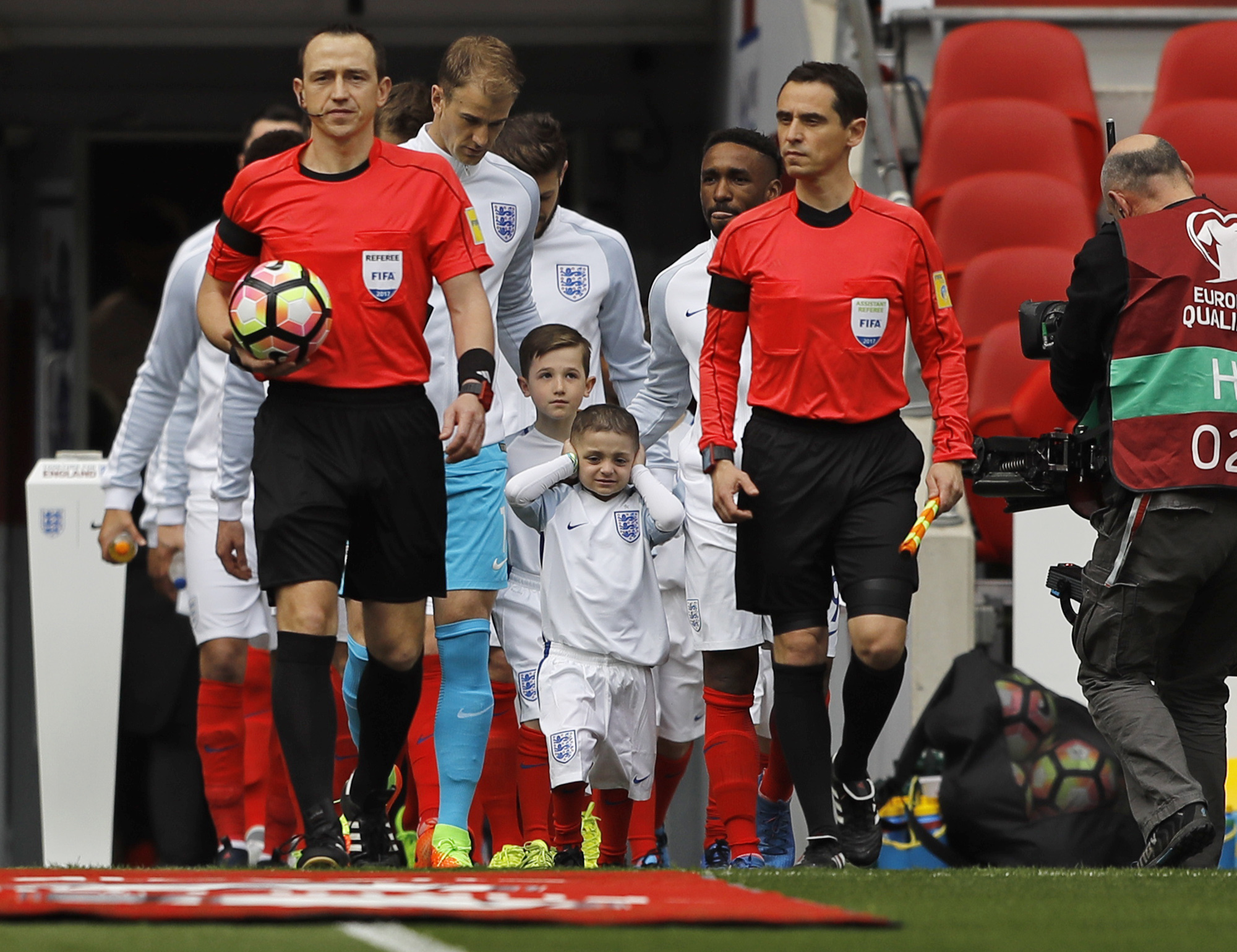 Bradley Lowery, battling a rare form of cancer, covers his ears while he is leading England out. Photo / AP
