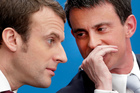 Former French Prime Minister Manuel Valls, right, speaks with former minister Emmanuel Macron in Paris. Photo / AP file