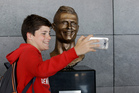 A boy takes a selfie next to the bust of Cristiano Ronaldo at the Madeira international airport outside Funchal, Portugal. Photo / AP.