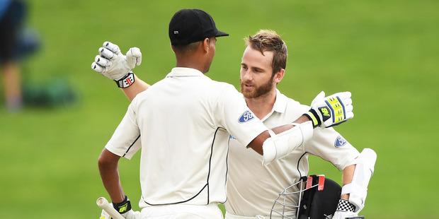 New Zealand captain Kane Williamson celebrates his century on Day 3 with Jeet Raval in Hamilton yesterday. Photo / Photosport