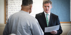 Prime Minister Bill English awards a certificate to a Paremoremo inmate  at a graduation ceremony at Auckland Prison today. Photo/ Jason Oxenham
