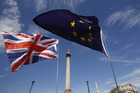 A Union Jack, left, and a European Union flag fly in front of Nelson's Column in Trafalgar Square during a Unite for Europe march to protest Brexit in central London. Photo / AP