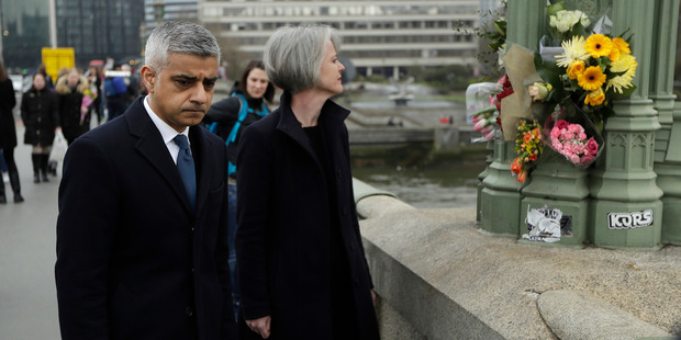 London Mayor Sadiq Khan stands on Westminster Bridge near floral tributes to victims of last week's attack outside the Houses of Parliament in London. Photo / AP