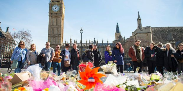 People look at floral tributes in Parliament Square yesterday. Photo / AP