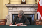 Britain's Prime Minister Theresa May signs the official letter to European Council President Donald Tusk, in 10 Downing Street, London yesterday. Photo / AP