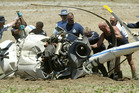 Police and emergency services try to move the wreckage of a Robinson R22 at Aratiatia in 2003. Photo / Alan Gibson