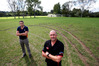 Central Brown president Darren Johnston, front, and vice-president Bryn Hughes with the damaged club pitch at Blue Goose. Photo / Michael Cunningham