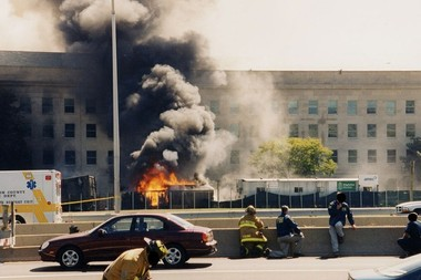 Firemen and FBI agents shelter behind barricades as flames rip through the Pentagon. Photo / FBI