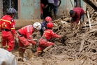 Rescue teams search through the mud and debris for survivors from the weekend landslide. Photo / AP
