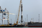A SpaceX rocket booster is hoisted off a barge after it arrived at Port Canaveral. Photo / AP