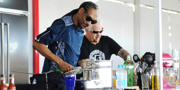 Snoop Dog and Chef Guy Fieri cook together during a demonstration at the South Beach Wine & Food Festival in Miami. Photo/AP