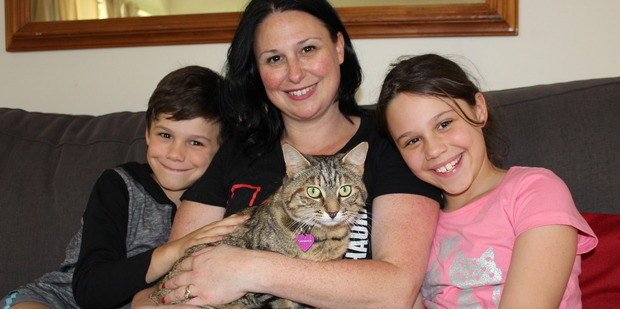 Tabby cat Cinnamon with Austen, left, Nicole and Madison Leach.