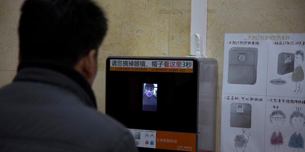 A man tries out a facial recognition toilet paper dispenser at a toilet in the Temple of Heaven park in Beijing. Photo / AP