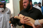 A man carrying a child following a suspected chemical attack. Photo / AP