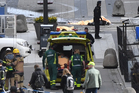 Emergency personnel load a person into an ambulance at the scene after a truck crashed into a department store injuring several people in central Stockholm. Photo / AP