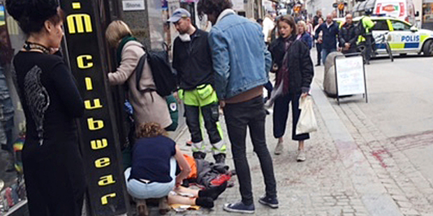 An injured person is helped near scene after a truck crashed into a department store injuring several people in central Stockholm. Photo / AP
