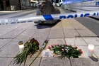 Candles and flowers are placed near the site where a truck crashed into a department store in central Stockholm. Photo / AP
