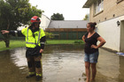 Pukete Senior station officer Dave O'Donnell talks with Sandwich Rd resident Bonnie Jobe about flooding around her home. Photo / Belinda Feek