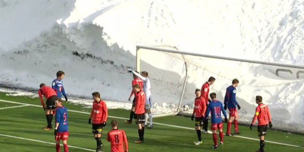 Loading Tromsdalen and Asane players play the match surrounded by the 20ft high wall of snow. Photo /Twitter - @Haneye