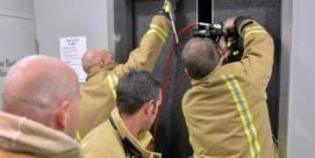 Firefighters trying to open the lift. Photo: Gerard O'Brien / Otago Daily Times