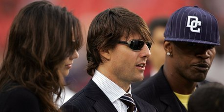 Tom Cruise, Katie Holmes and Jamie Foxx stand on the field before a football game. Photo / Getty