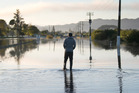 A person walks through the streets of a flooded Edgecumbe last week. Photo / Alan Gibson.