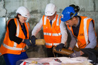 Maggie Barry, with help from Heritage NZ chief executive Andrew Coleman (centre) and contractor Russell Molder, manages to prise the contents from the time capsule. Photo Mark Mitchell.