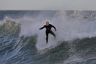 Surfers make the most of giant swells at Mt Maunganui main beach today. Photo / John Borren