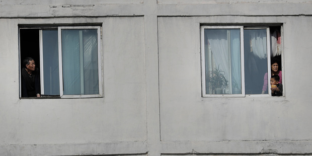 North Koreans watch runners of the Pyongyang marathon from their apartment windows. Photo / AP