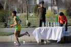 A North Korean military soldier stands on duty while a participant of the Pyongyang marathon runs past a water station. Photo / AP