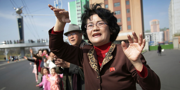 Sin Ye Suk, 50, a resident of Mirae Scientist Street stands in front of her apartment with fellow residents as they cheer on participants of the Pyongyang marathon. Photo / AP