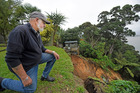 Omokoroa resident John Cufflin, who lives in Kowhai Grove, kneeling at the edge of the major slip which is creeping closer to his and his neighbours' homes. Photo/File.