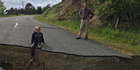 Jack Satterthwite sits on the lip of a large crack in the road in Waiau, North Canterbury, caused by the 7.8 earthquake that struck just after midnight on November 14. Photo / File