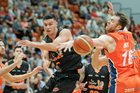 Hawks co-skipper Jarrod Kenny deftly slips a pass between Sharks players Luke Aston (left) and import Nick Kay in the NBL match at the PG Arena, Napier, tonight. Photo/Warren Buckland