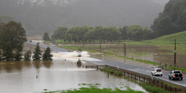 Loading Cars negotiate floodwaters on State Highway 10 just north of the Whangaroa Bridge. Photo/Peter de Graaf