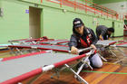 Nancy Kareroa-Yorke of Northland Red Cross helps set up a bed for evacuated families in the Whakatane Memorial Hall. PHOTO/SUPPLIED