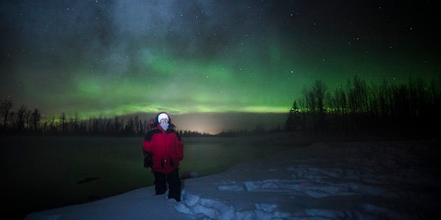 Anna Harrison in Alaska, with the Northern Lights above her. Photo / Jody Overstreet