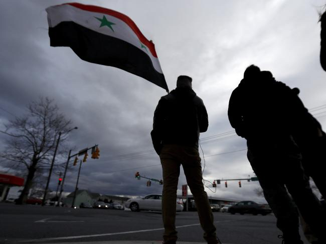 A man holds a Syrian flag during a rally in opposition to the US missile strikes in Syria in Allentown, Pennsylvania. Allentown has one of the nation's largest Syrian populations. They are mostly Christian and support Syrian President Bashar al-Assad. Photo/AP