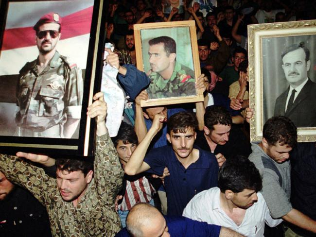 Syrians hold portraits of President Hafez Assad (right) son Bashar (centre) and son Bassel, following the President's death in 2000. Photo/AP