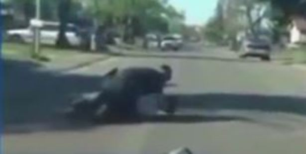 An unidentified policeman tackles Nandi Cain to the ground for jaywalking.