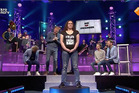 A woman stands on a spinning podium while men guess if she's