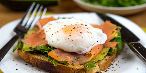 A high fat breakfast is best - poached eggs, salmon and avocado on toast. Photo / 123RF