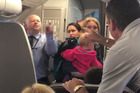 A video showing an American Airlines employee challenging a passenger to hit him after a woman holding a baby was allegedly hit with her stroller has surfaced.