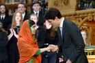 Pakistani activist and Nobel Peace Prize winner Malala Yousafzai, left, speaks to Canadian Prime Minister Justin Trudeau after being presented with an honourary citizenship. Photo / AP