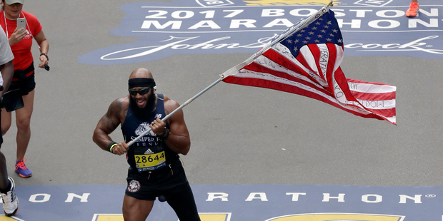 Jose Sanchez, of San Antonio, carries the United States flag across the finish line in the 121st Boston Marathon. Photo / AP