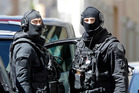 Hooded police officers patrol outside a building during searches in Marseille, southern France. Photo / AP