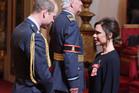 Fashion designer Victoria Beckham, right, receives her OBE from Britain's Prince William. Photo / AP